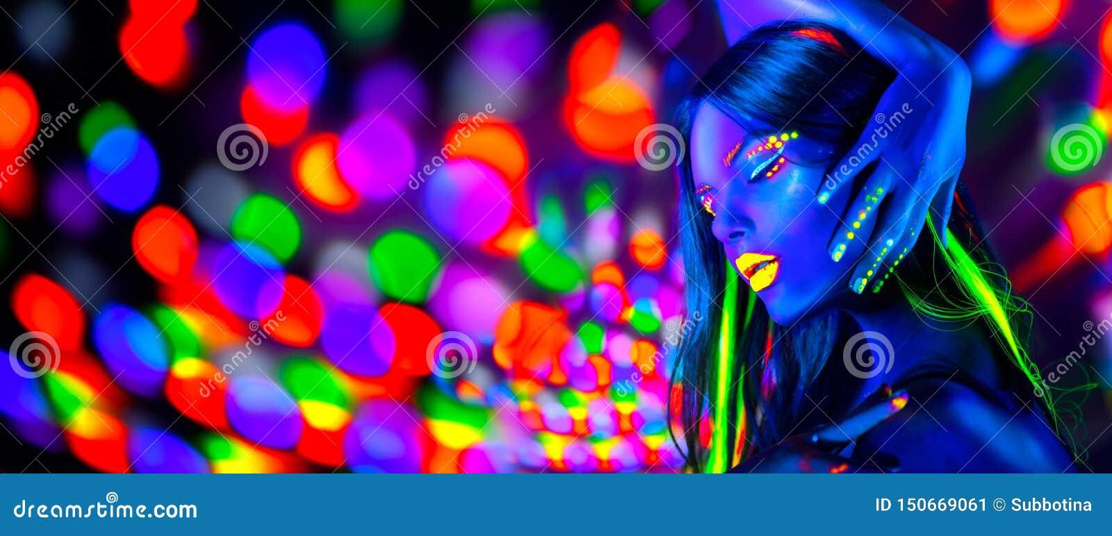Сексуальные танцы девушки в неоновых светах Женщина фотомодели с дневным макияжем представляя в УЛЬТРАФИОЛЕТОВОМ