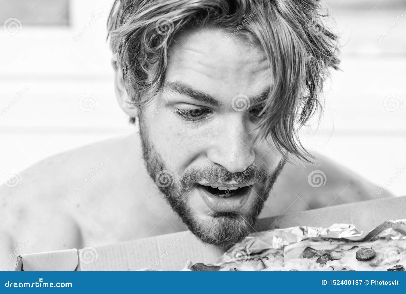 Сексуальный человек ест пиццу лежа на кровати Студент дома на кровати в яркой квартире есть вкусную пиццу Человек бородатый