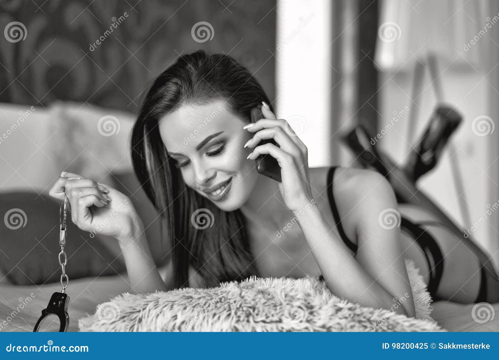 Download Сексуальная женщина в удерживании кровати надевает наручники и вызывающ черно-белый Стоковое Изображение - изображение насчитывающей пятки, сообщение: 98200425