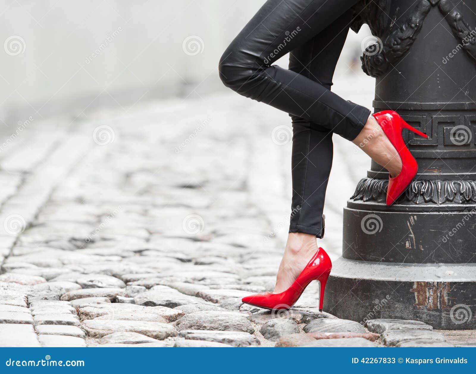 Сексуальная женщина нося красные ботинки высокой пятки в городе