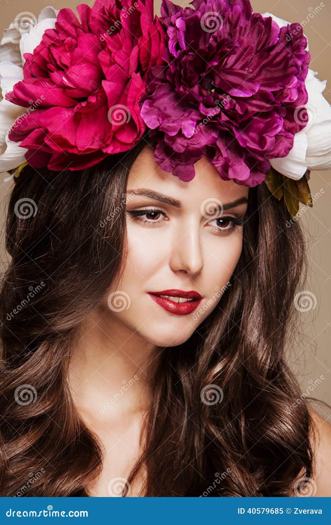 Сексуальная красивая женщина с яркими цветками на ее голове
