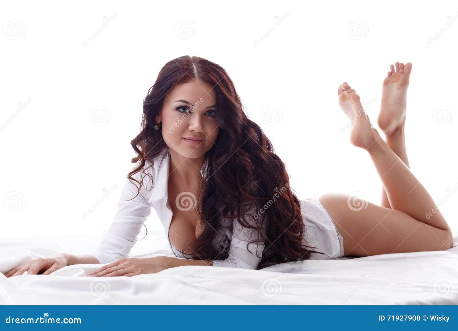 Сексуальное брюнет смотря камеру пока лежащ в кровати
