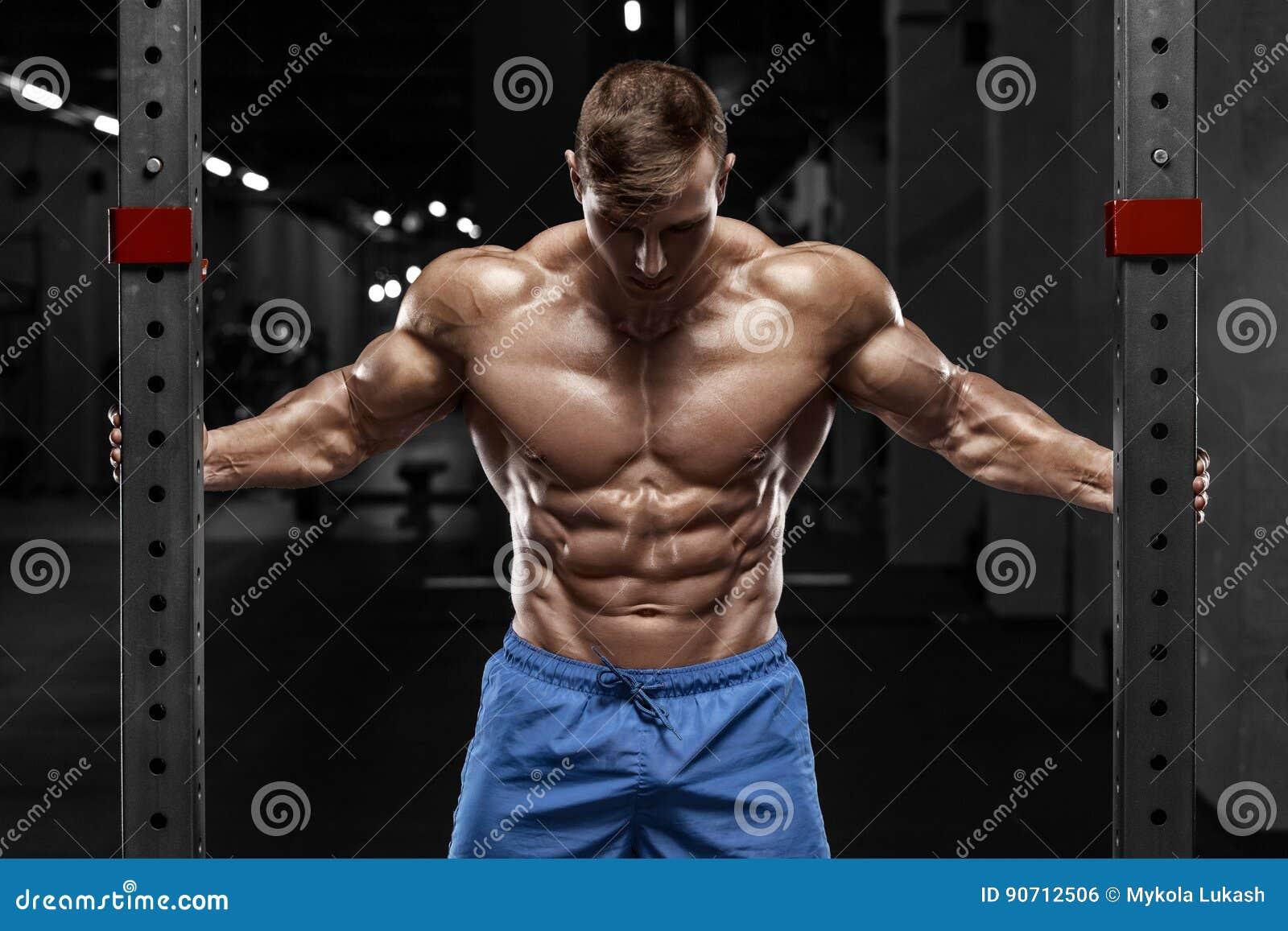 Сексуальный мышечный человек в спортзале, форменное подбрюшном Сильный мужской нагой abs торса, разрабатывая