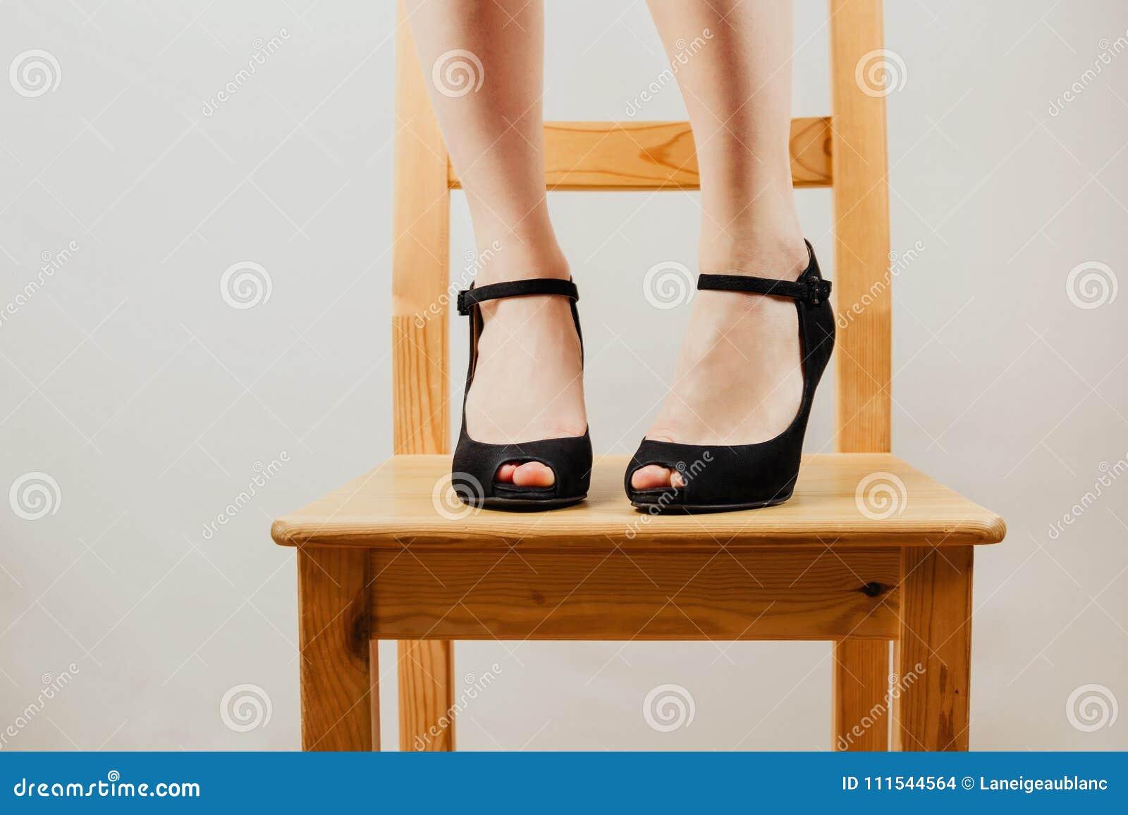 Селективная съемка ног ` s белой женщины в черном максимуме накренила ботинки стоя на деревянном стуле