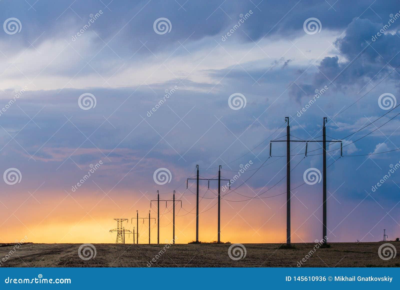 Сельский ландшафт с линией высокого напряжения на заходе солнца