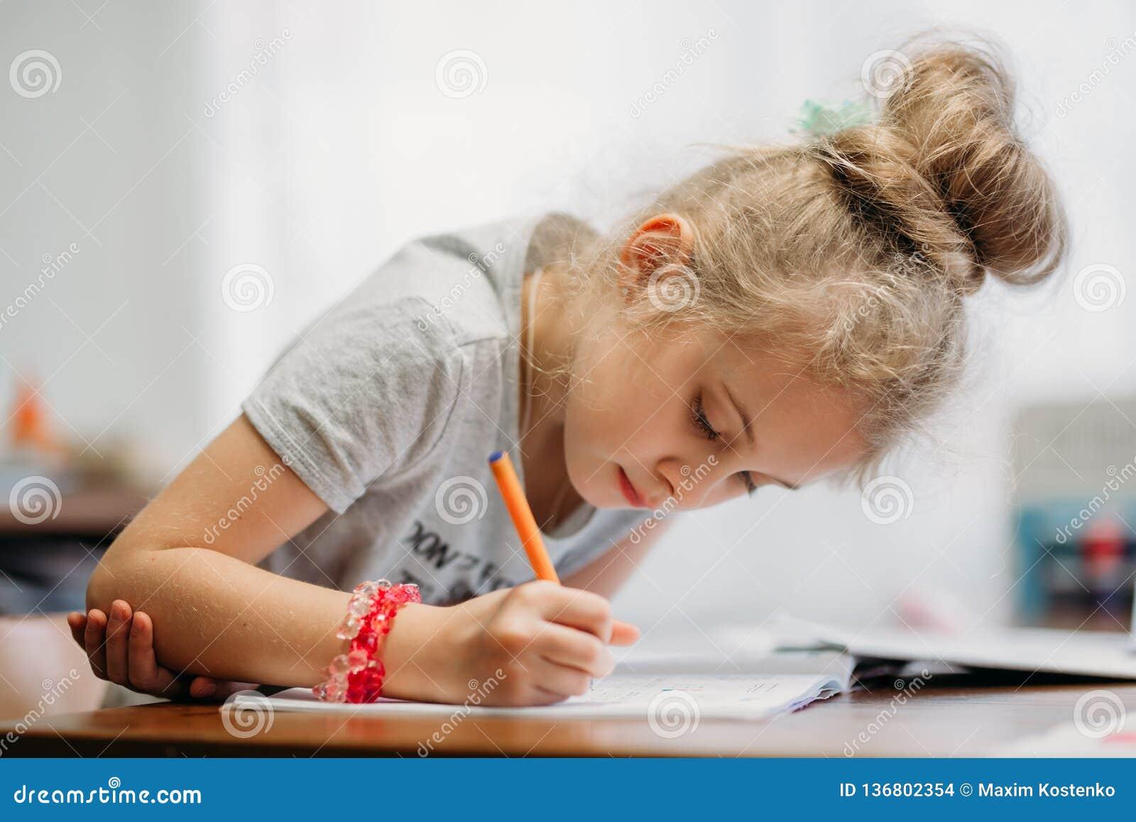 Семилетняя девушка сидит дома на таблице и пишет в тетради, завершая уча задачу или повторяя уроки