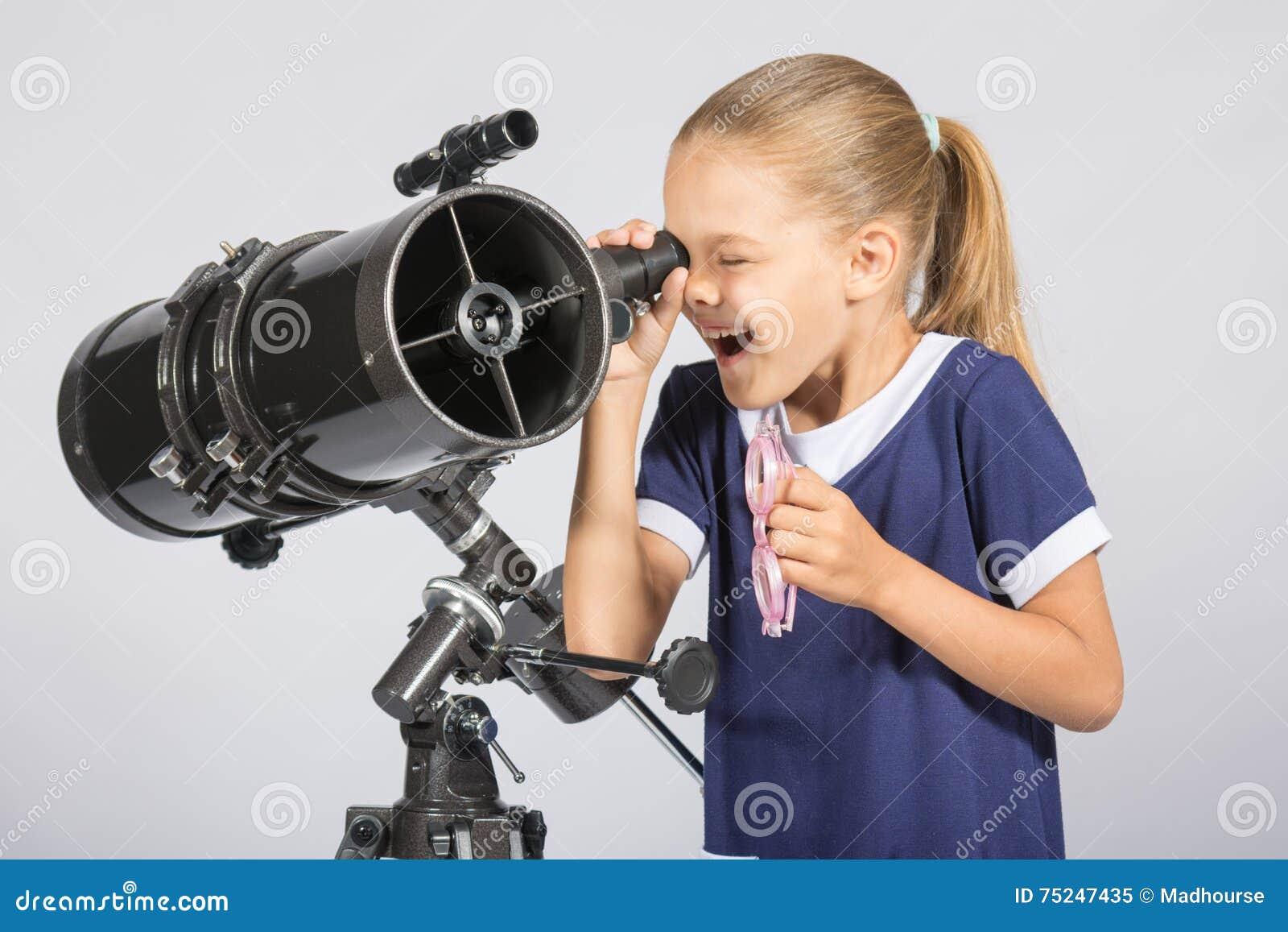 Семилетняя девушка с интересом и смотреть рта открытым в телескоп рефлектора и взглядами на небе