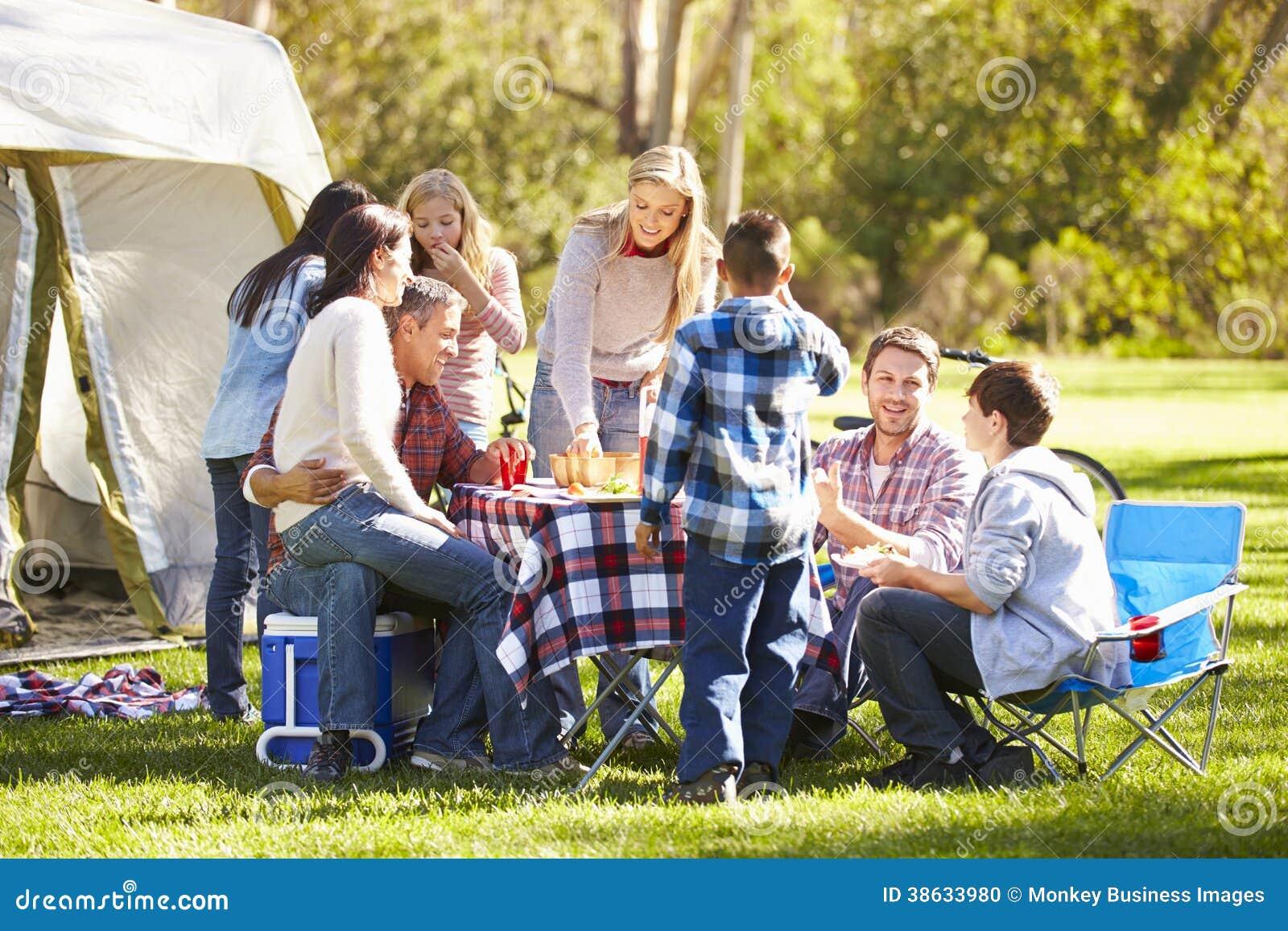 2 семьи наслаждаясь располагаясь лагерем праздником в сельской местности