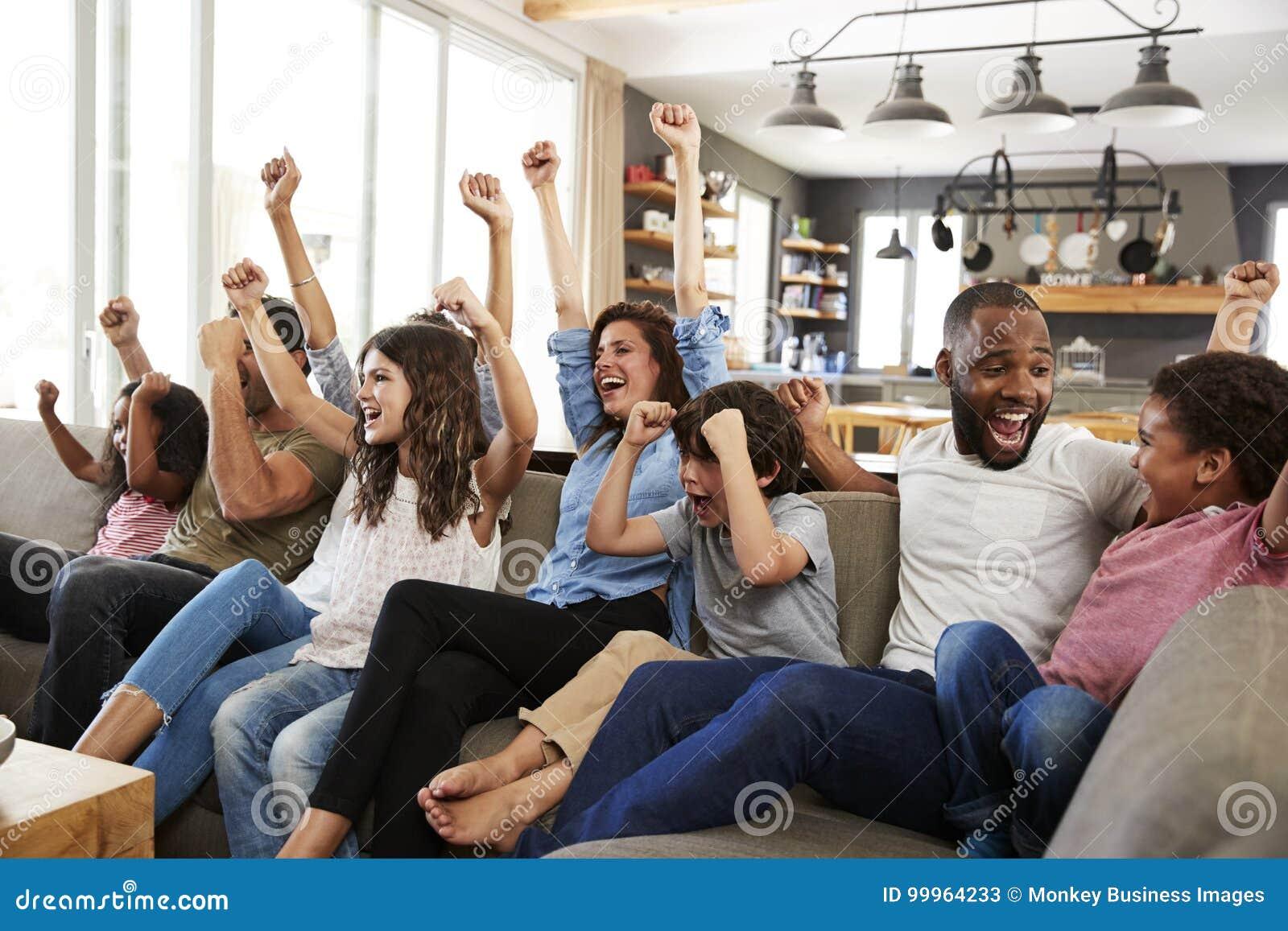 2 семьи смотря спорт на телевидении и веселить