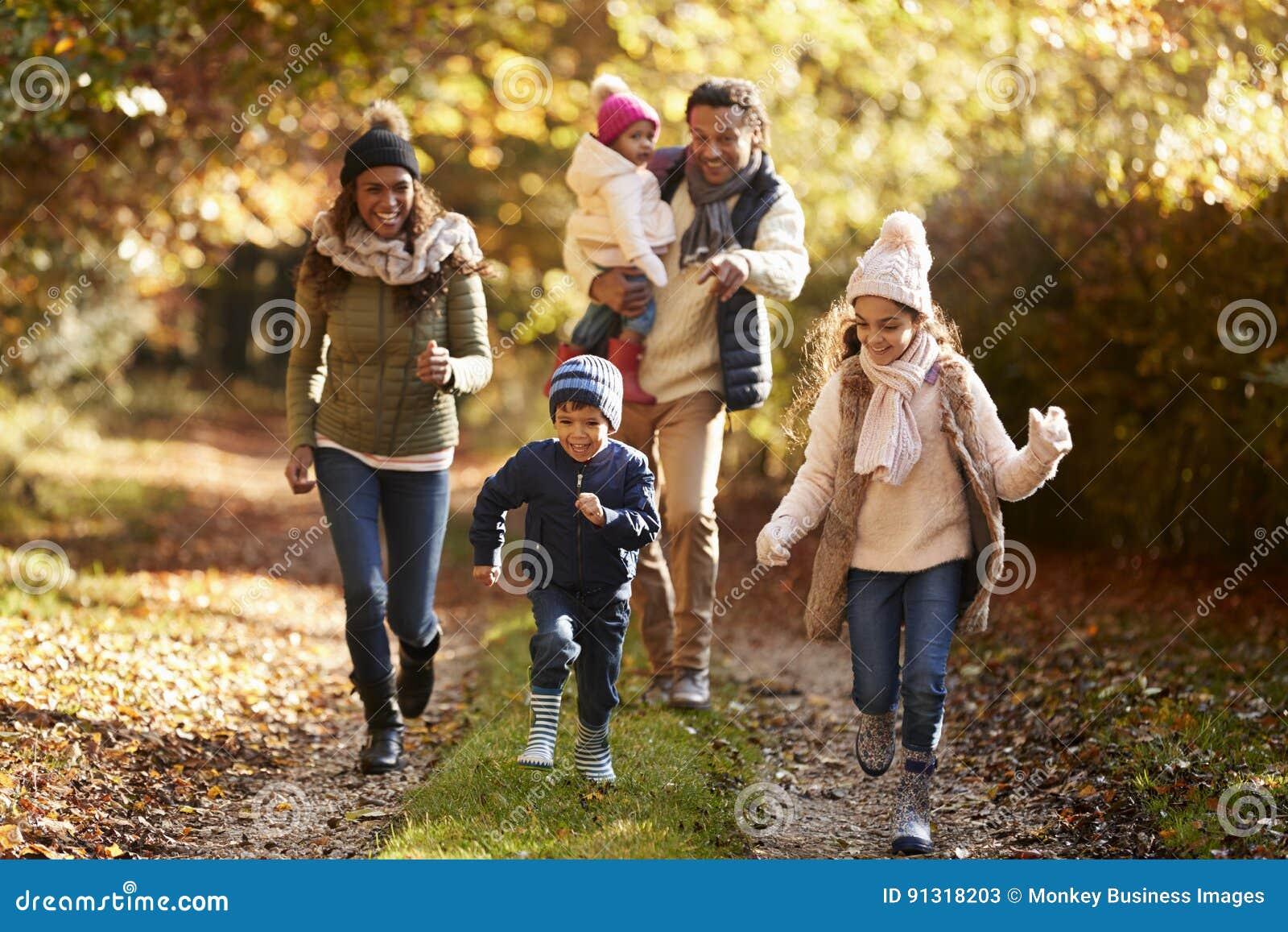 Семья бежать вдоль пути через сельскую местность осени