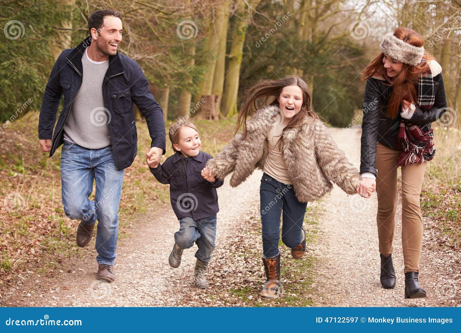 Семья бежать на прогулке сельской местности зимы совместно