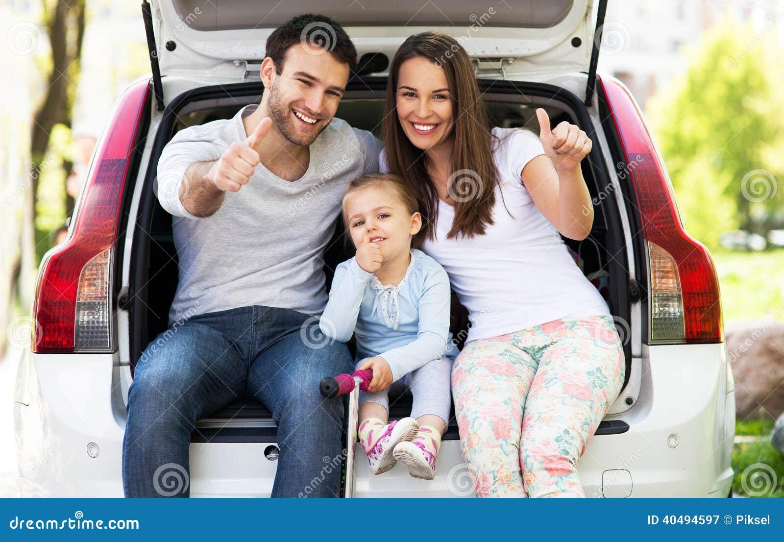 Семья в автомобиле показывая большие пальцы руки вверх