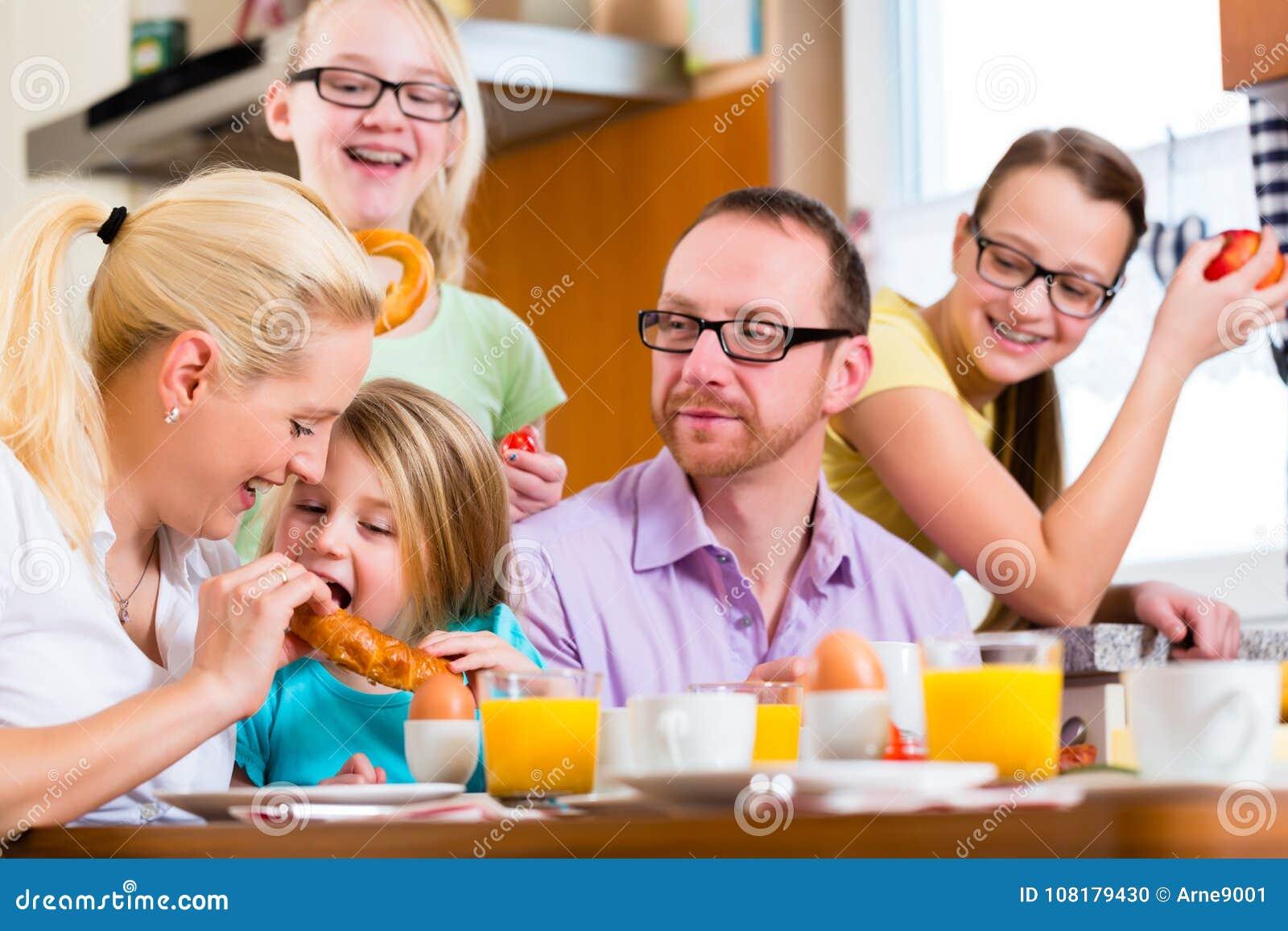 Семья в кухне имея завтрак совместно