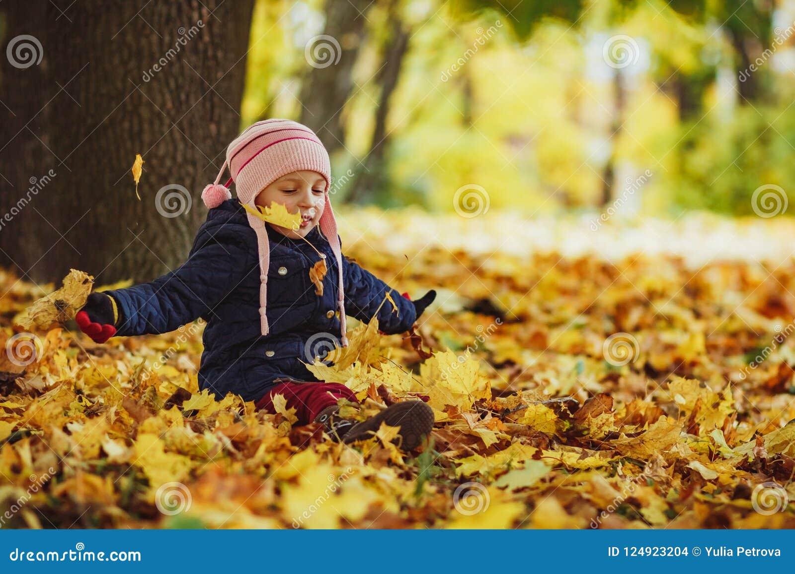 Семья, детство, сезон падения и концепция людей, счастливая девушка играя с листьями осени в парке маленький ребенок, ребёнок
