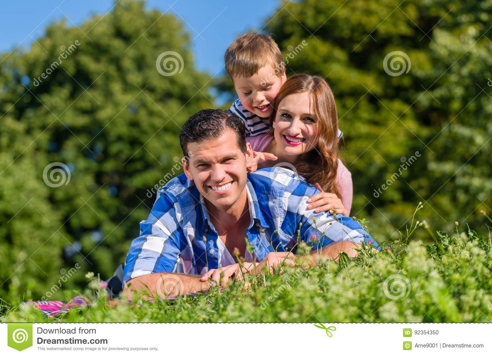 Семья лежа в траве na górze одина другого