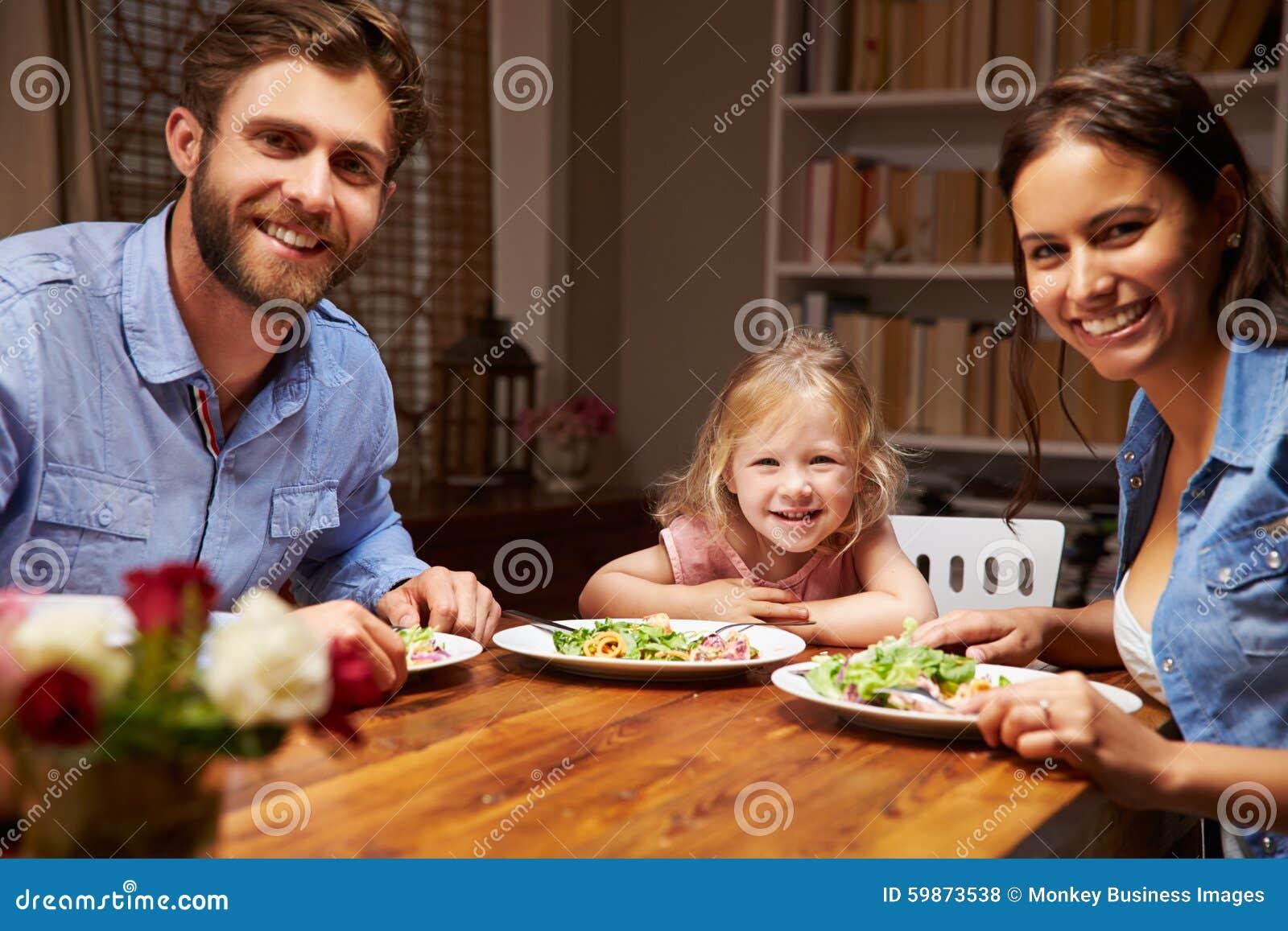 Семья есть обедающий на обеденном столе, смотря камеру