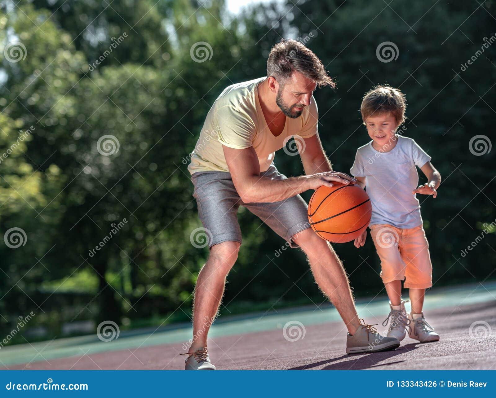 Семья играя баскетбол outdoors