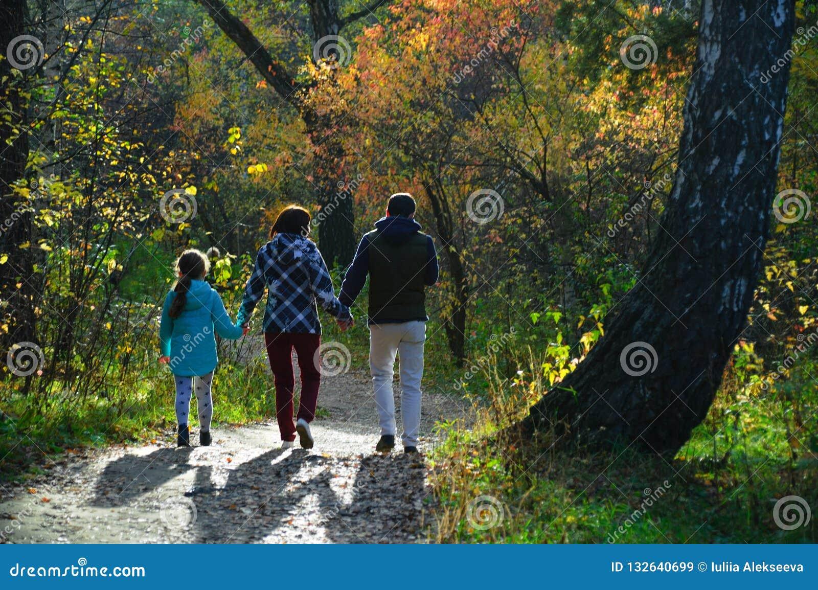 Семья идет в лес осени