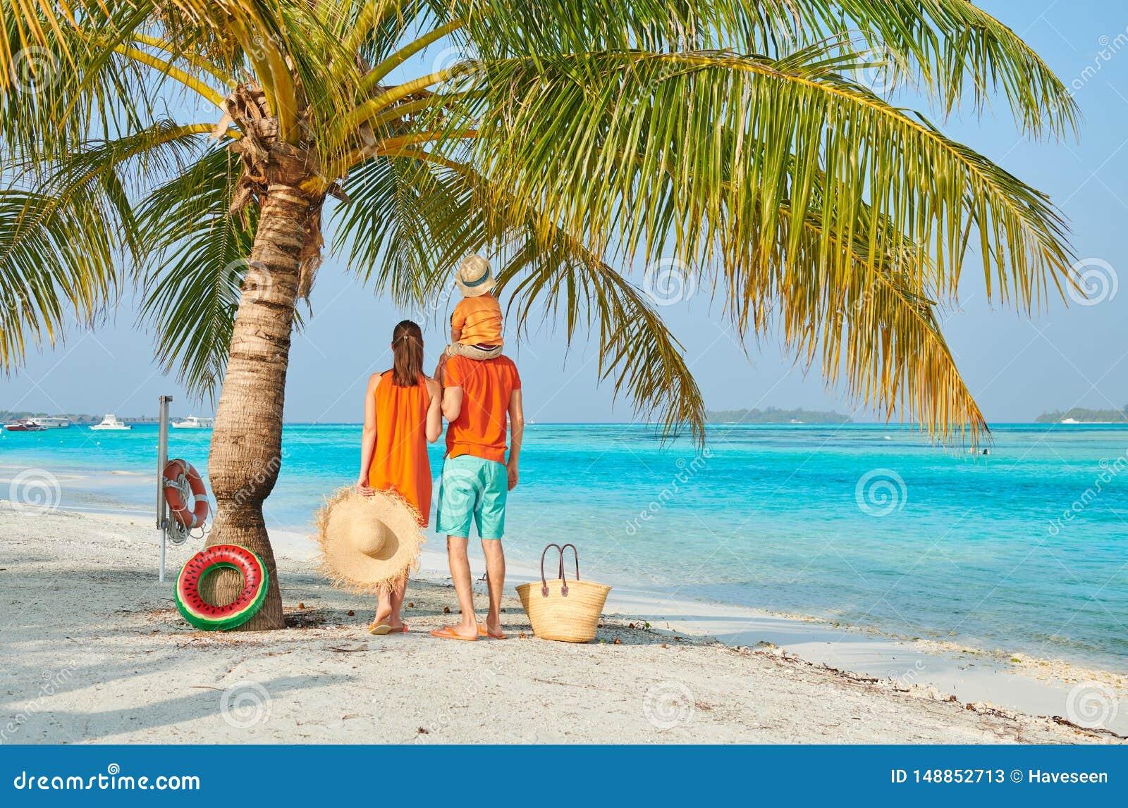 Семья из трех человек на пляже под пальмой