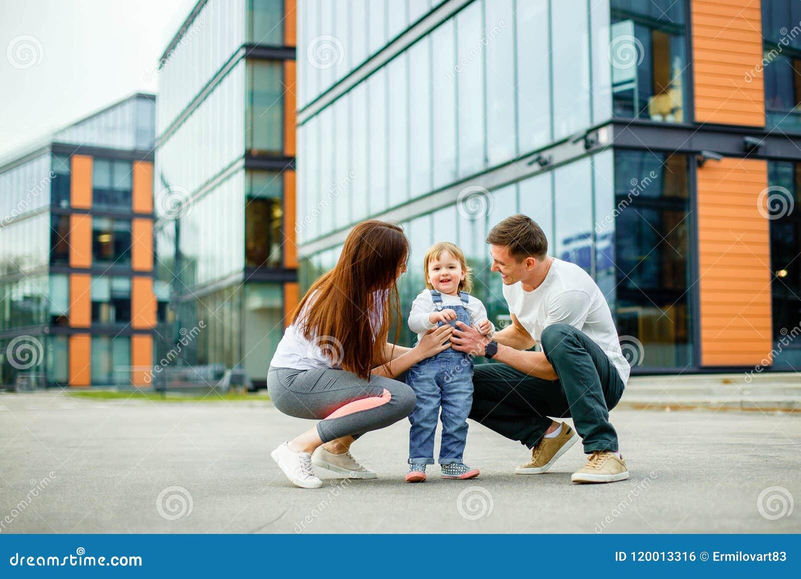 Семья из трех человек портрета счастливая Играть молодых родителей усмехаясь с их маленькой дочерью пока идущ через улицы