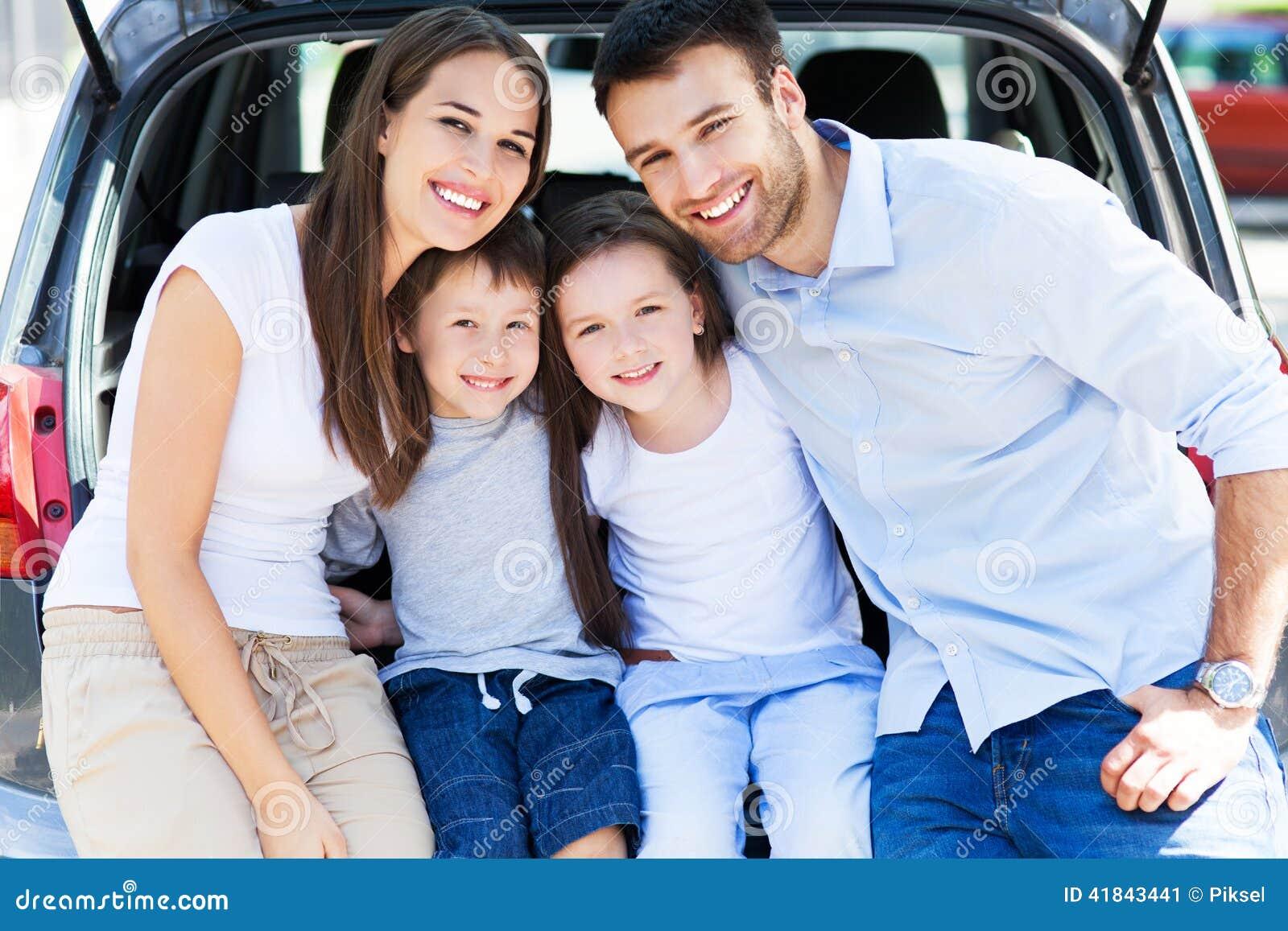Семья из четырех человек сидя в багажнике автомобиля