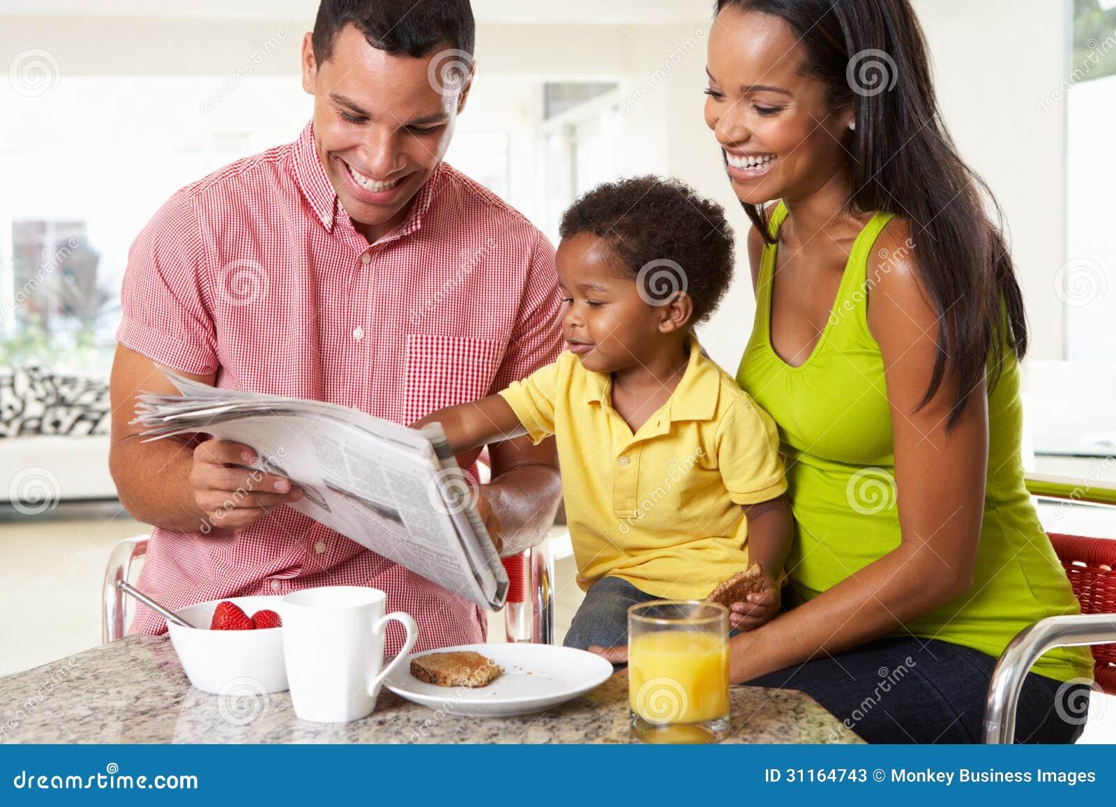 Семья имея завтрак в кухне совместно