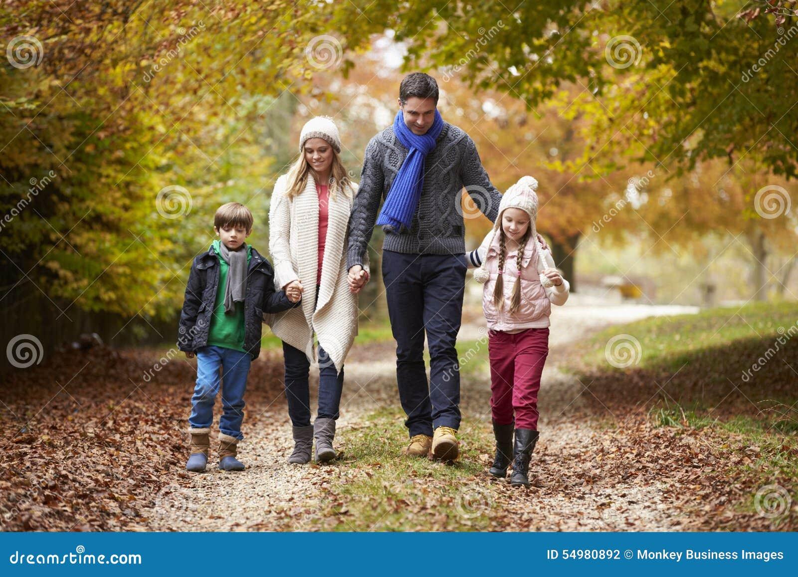 Семья идя вдоль пути осени
