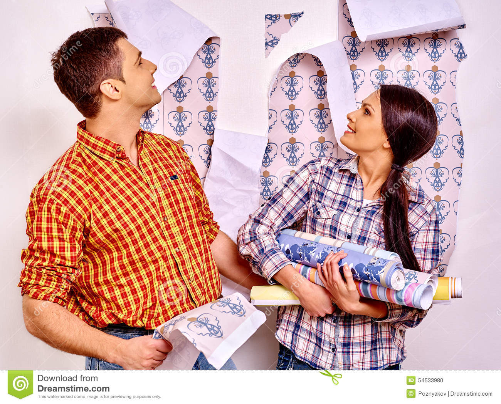 Семья клеит обои дома