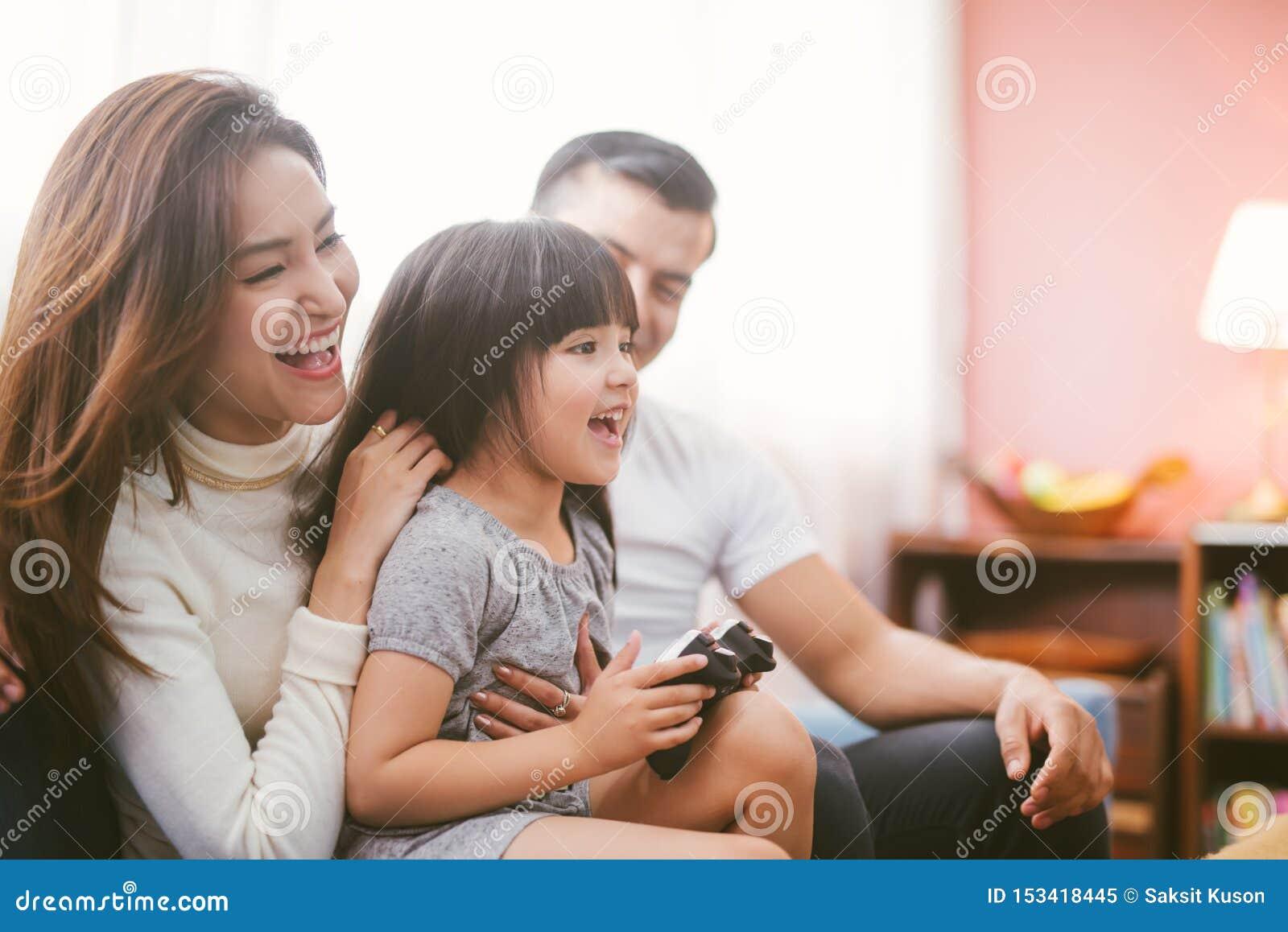 Семья маленькой девочки и родителя играя видеоигру дома