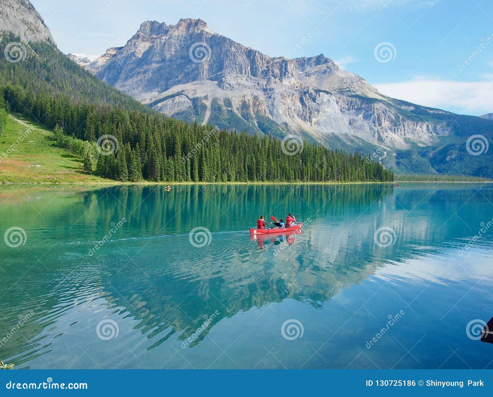 Семья на путешествии Kanu в изумрудном озере в национальном парке Yoho,