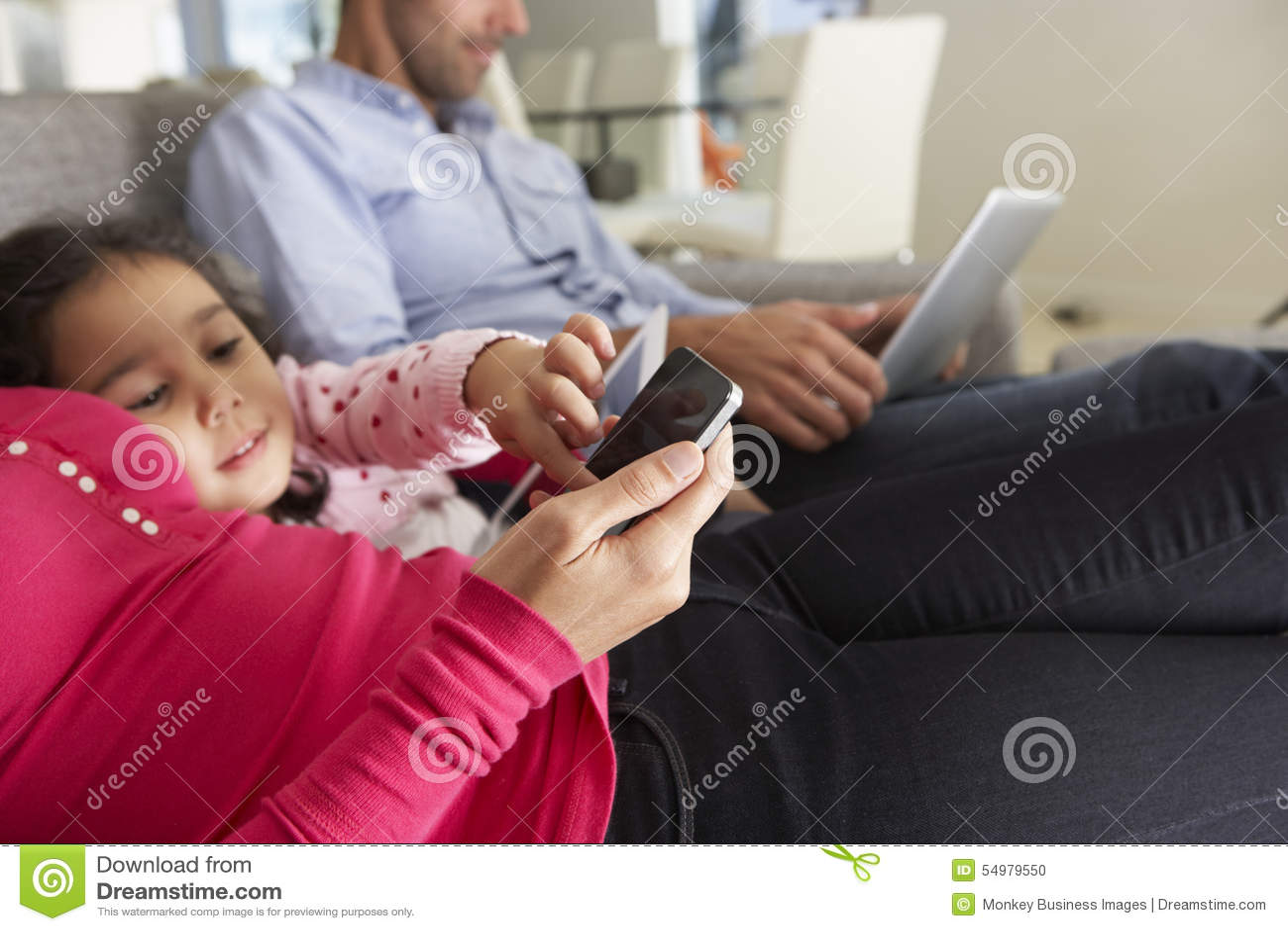 Семья на софе с Smartphone, компьтер-книжкой и таблеткой цифров