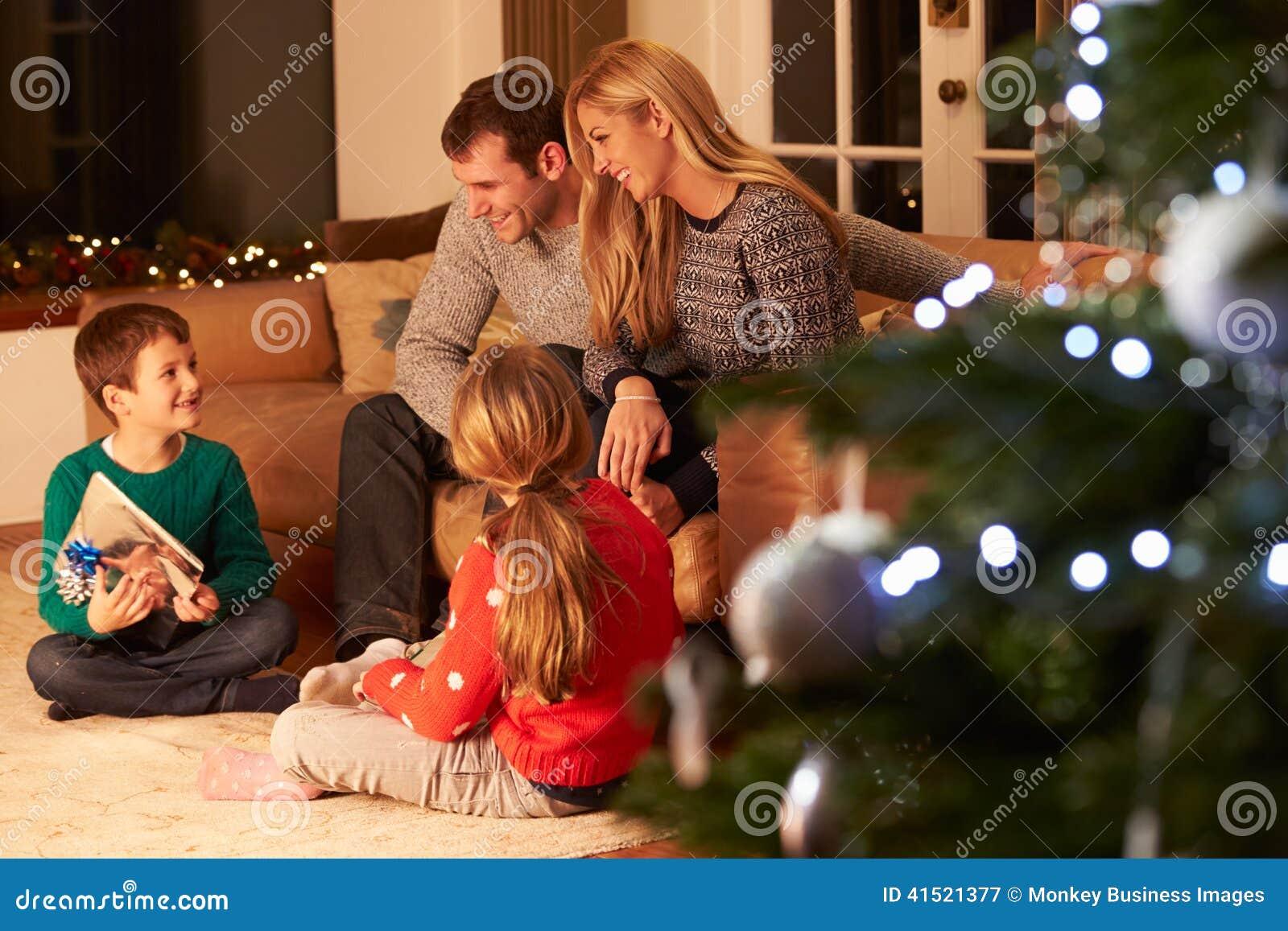 Семья обменивая подарки рождественской елкой