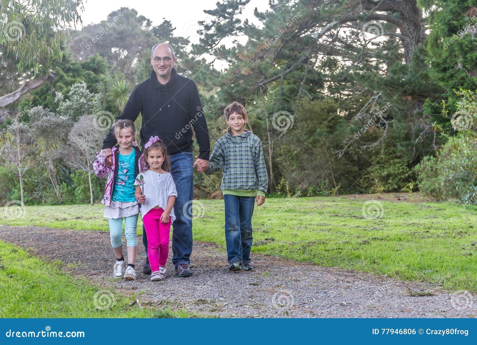 Семья - отец и дети - в парке
