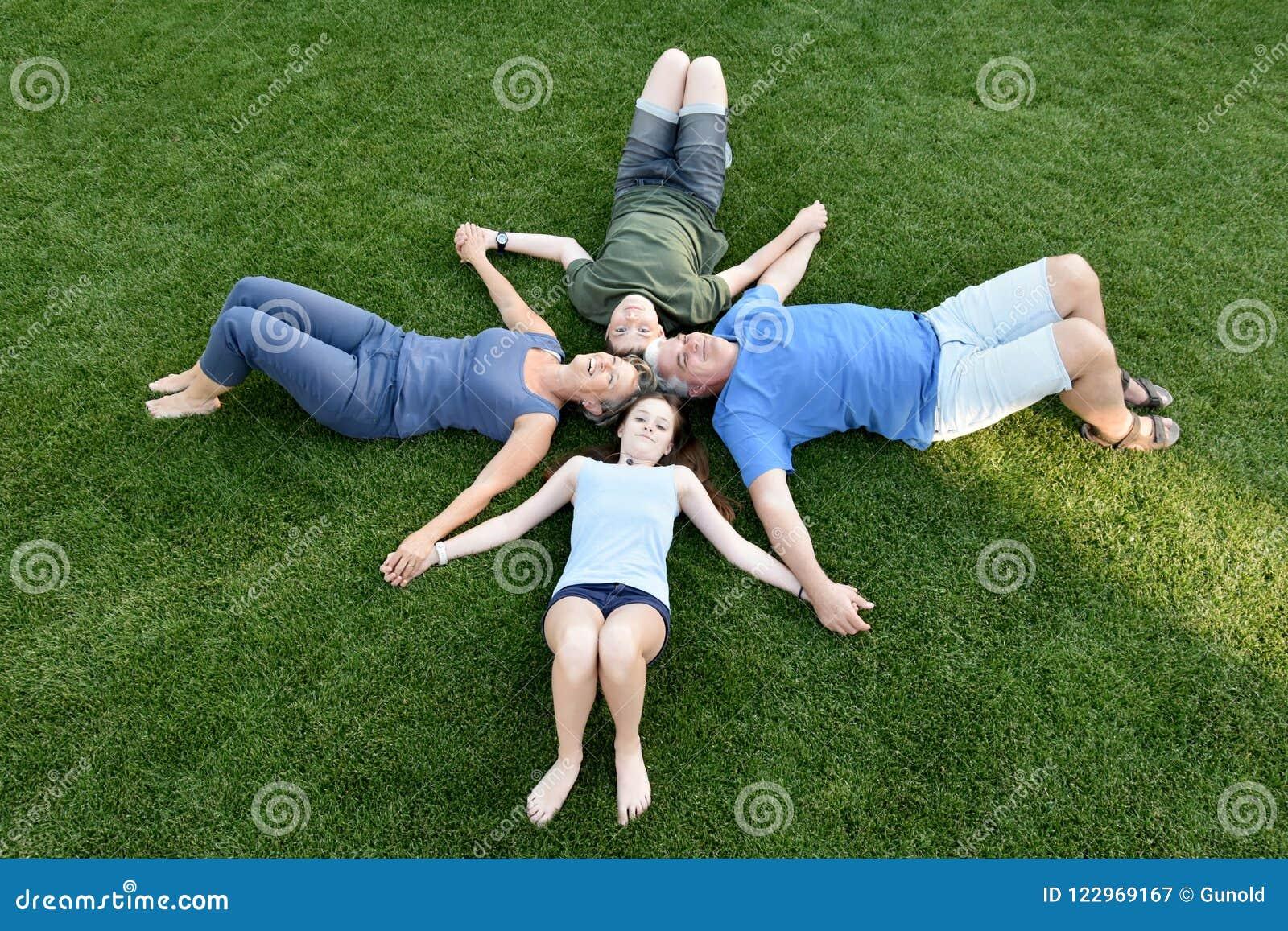 Семья, отец, мать, сын и дочь лежа в луге