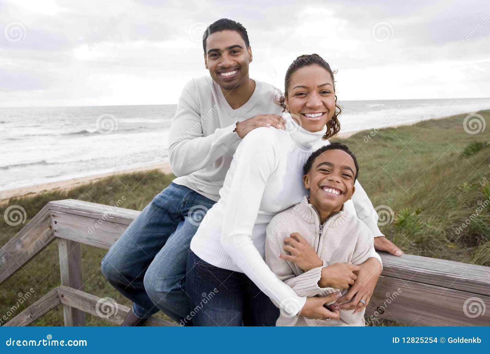 семья пляжа афроамериканца обнимая усмехаться
