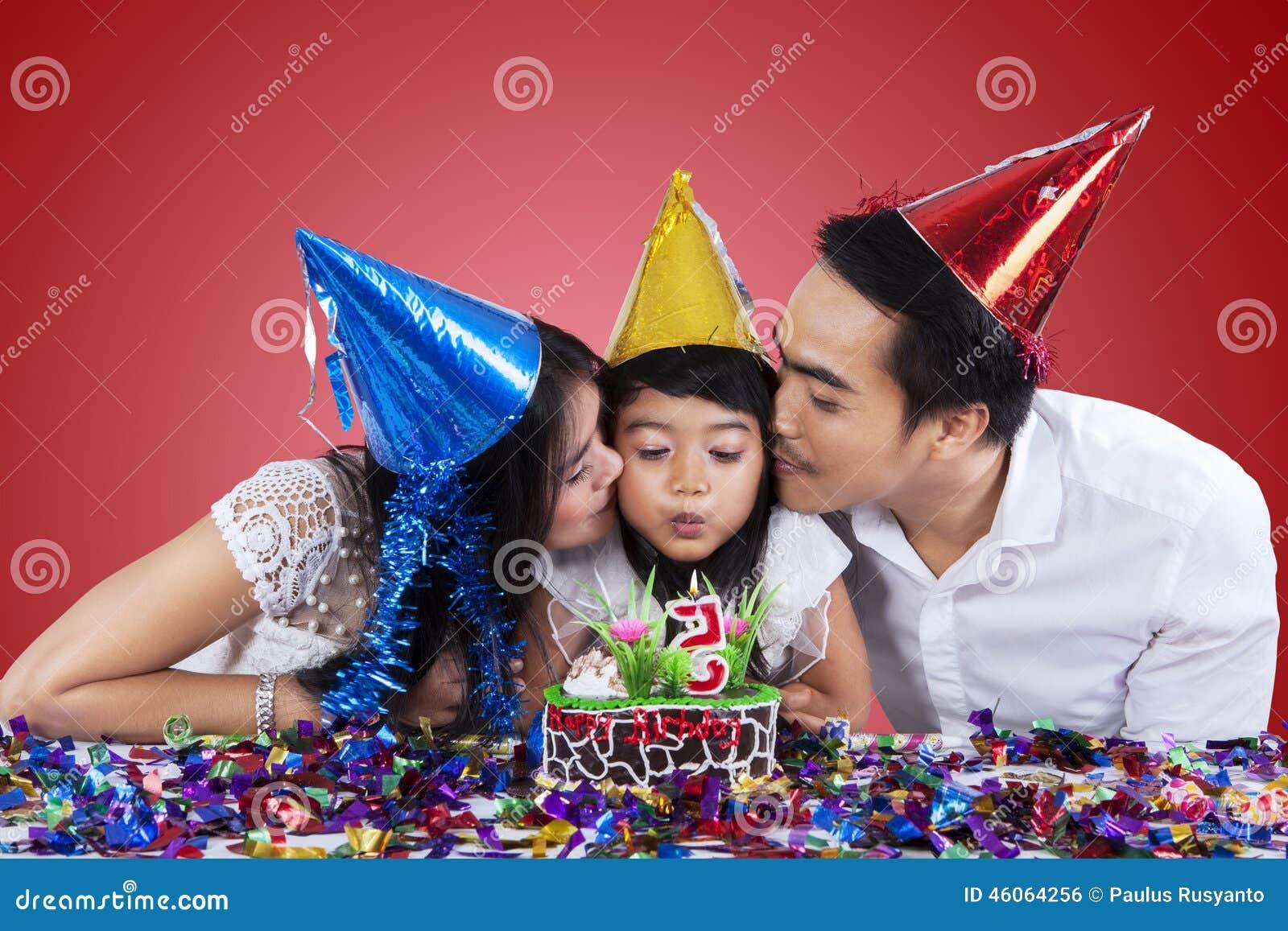 Семья празднует день рождения с красной предпосылкой