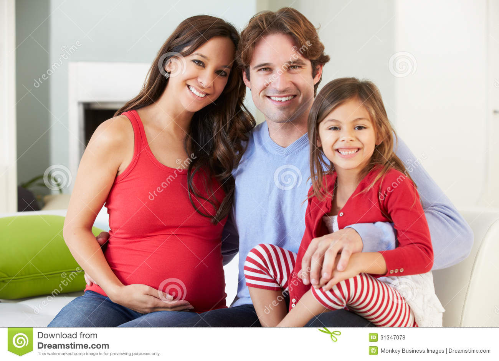 Семья при беременная мать ослабляя на софе совместно