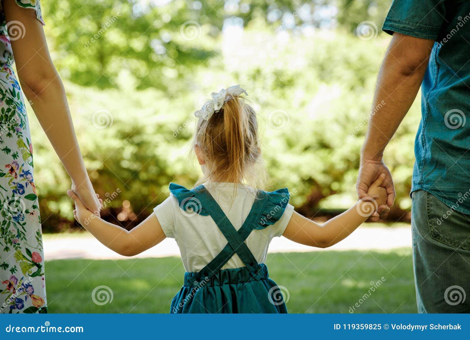 Семья, родительство, принятие и концепция людей Счастливые мать, отец и маленькая девочка идя в лето паркуют