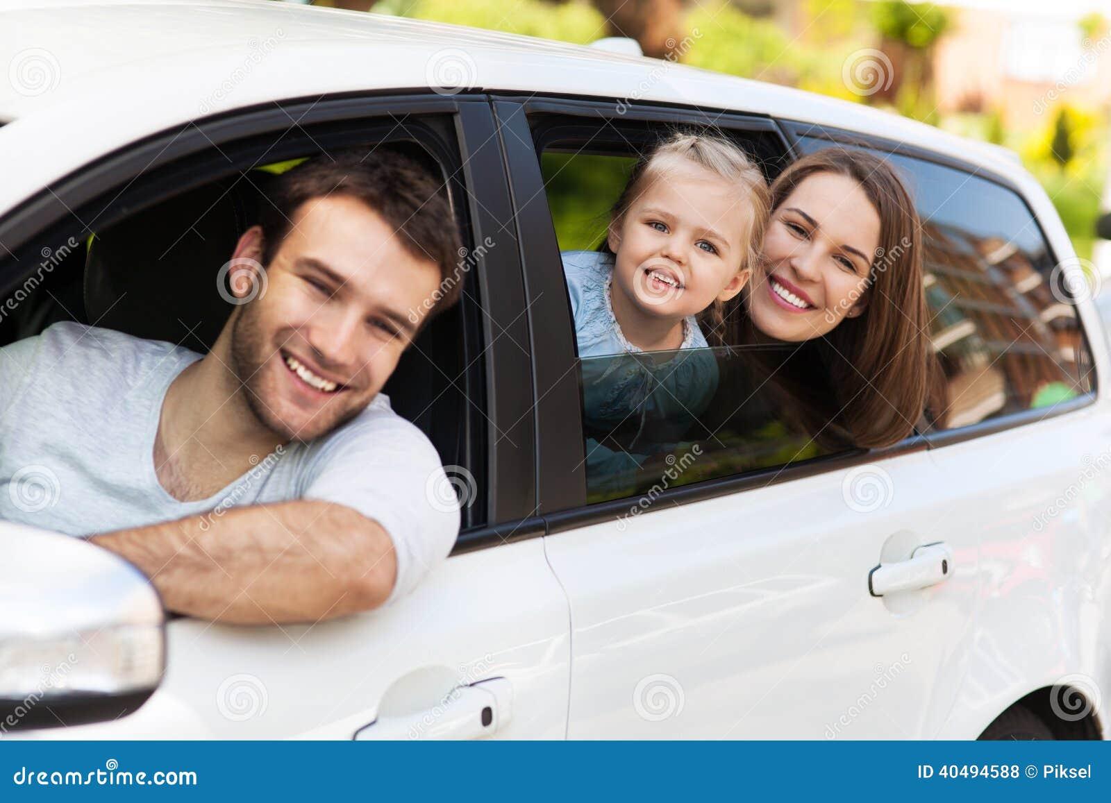 Семья сидя в автомобиле смотря вне окна