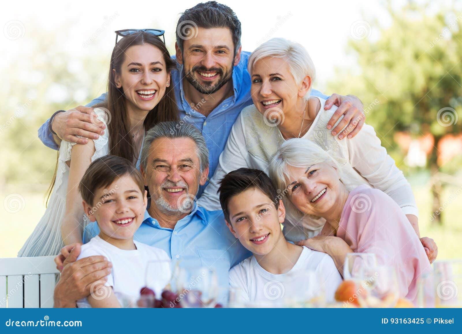 Семья сидя на таблице outdoors, усмехающся