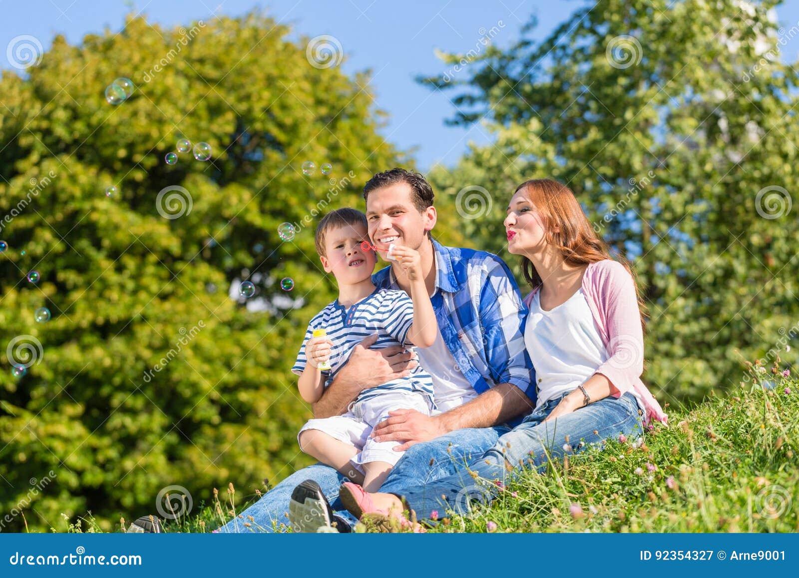 Семья сидя на луге играя с пузырями мыла
