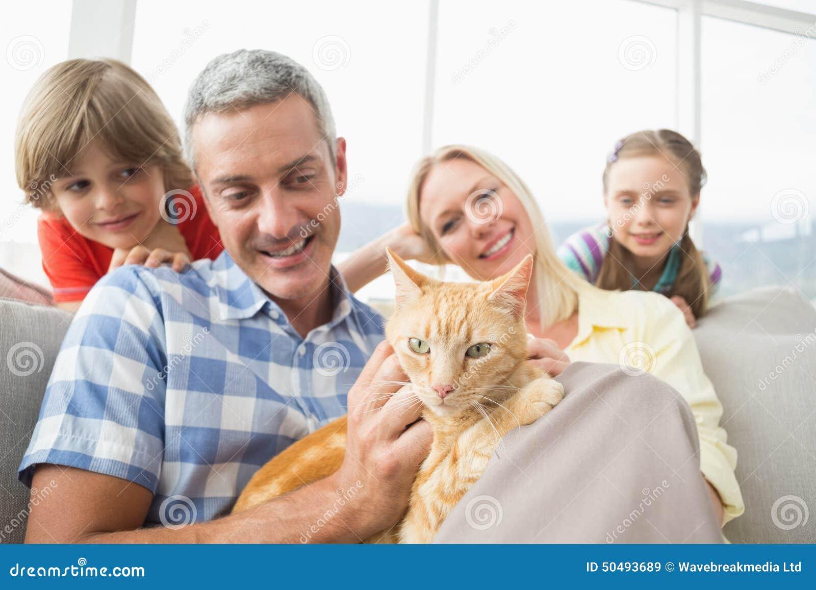 Семья сидя с котом на софе дома