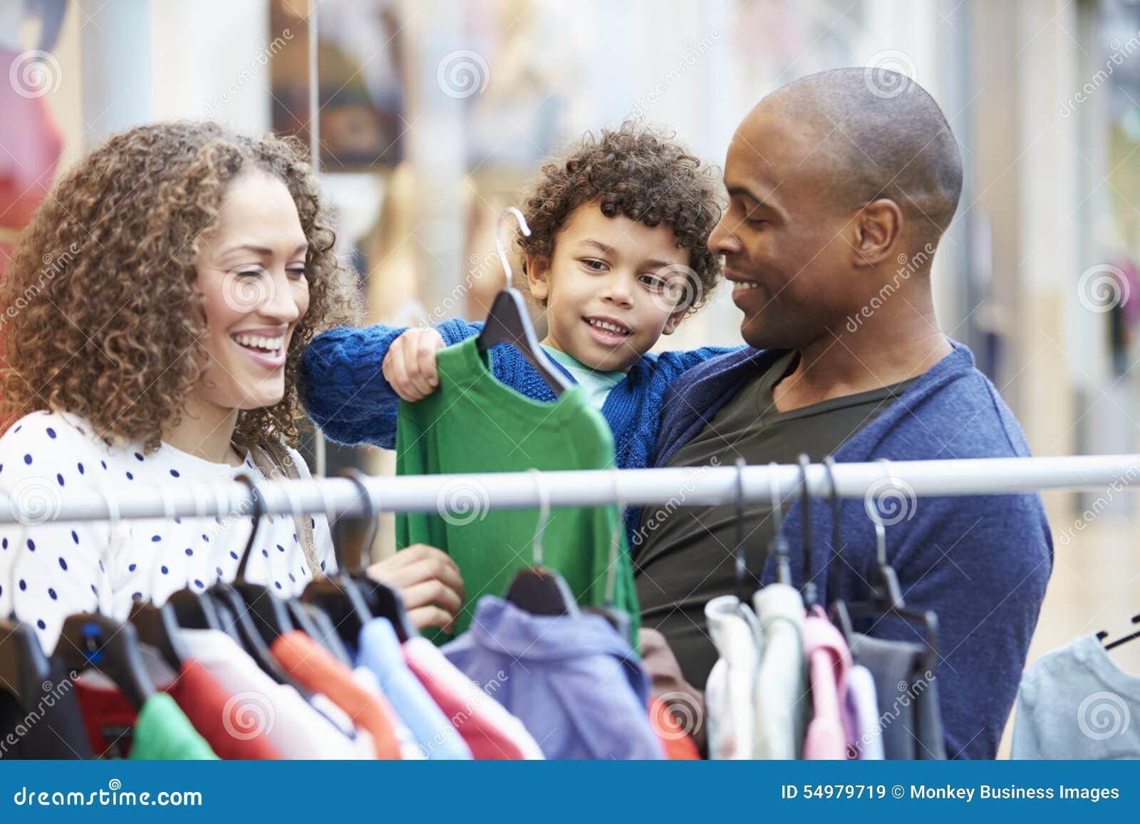 Семья смотря одежды на рельсе в торговом центре