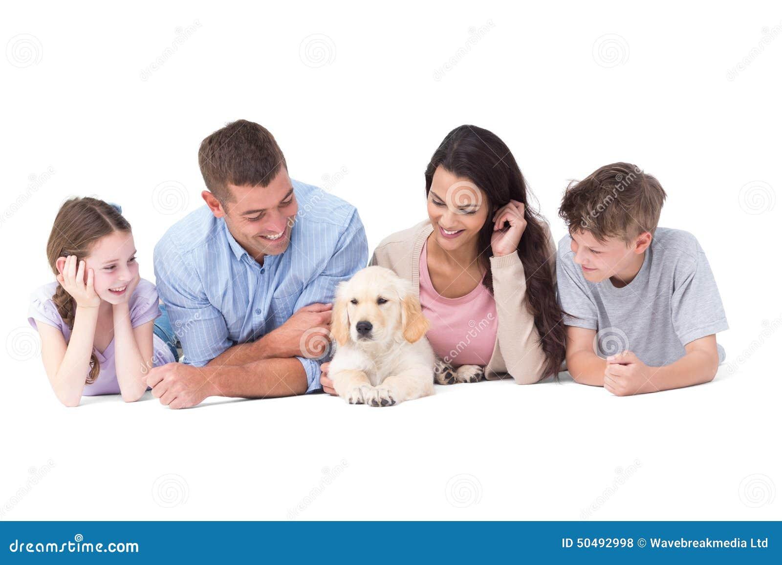 Семья смотря щенка пока лежащ