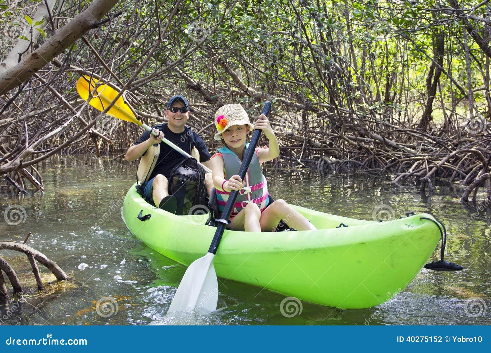 Семья сплавляться через тропический лес мангровы
