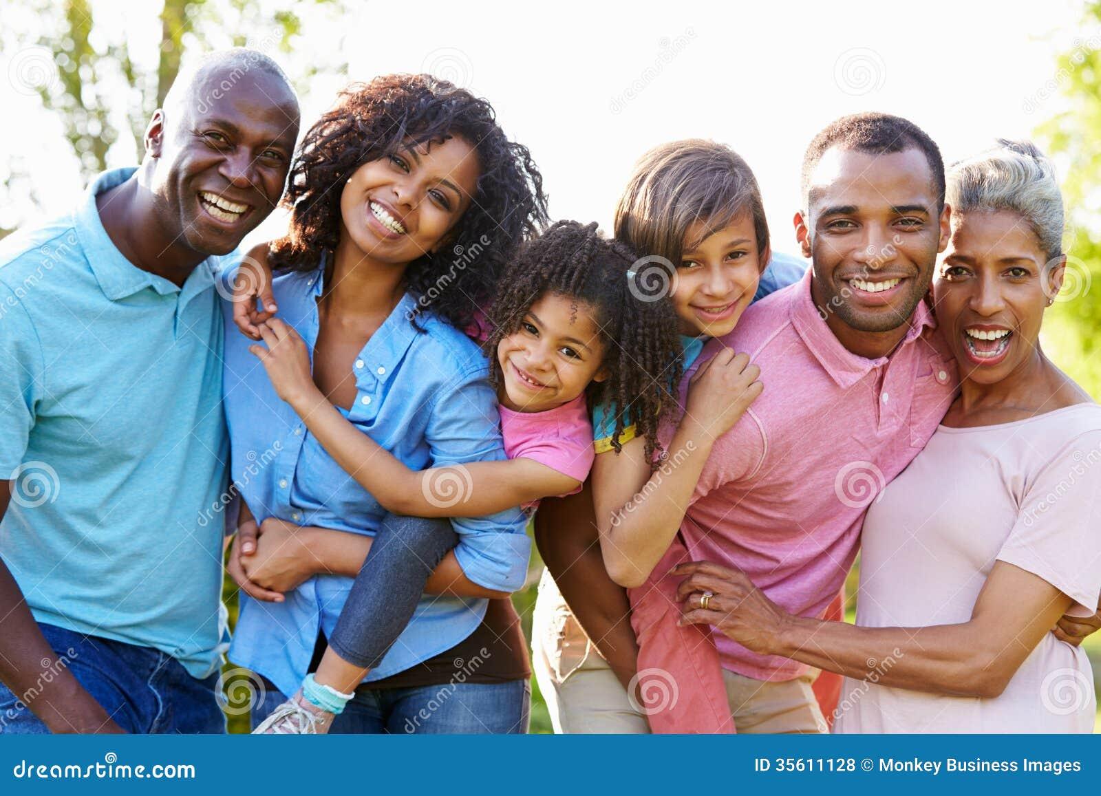 Семья Multi поколения Афро-американская стоя в саде