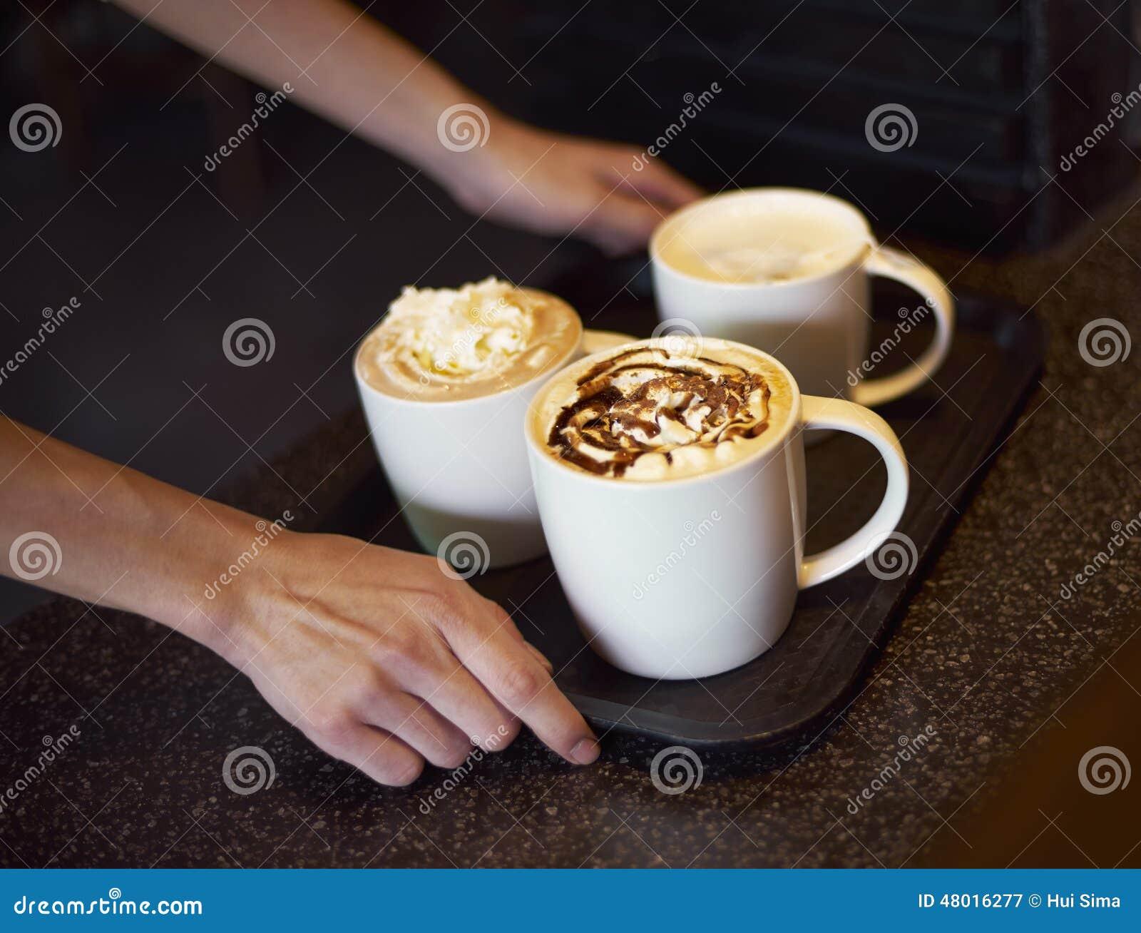 Сервер кофейни поставляя кофе