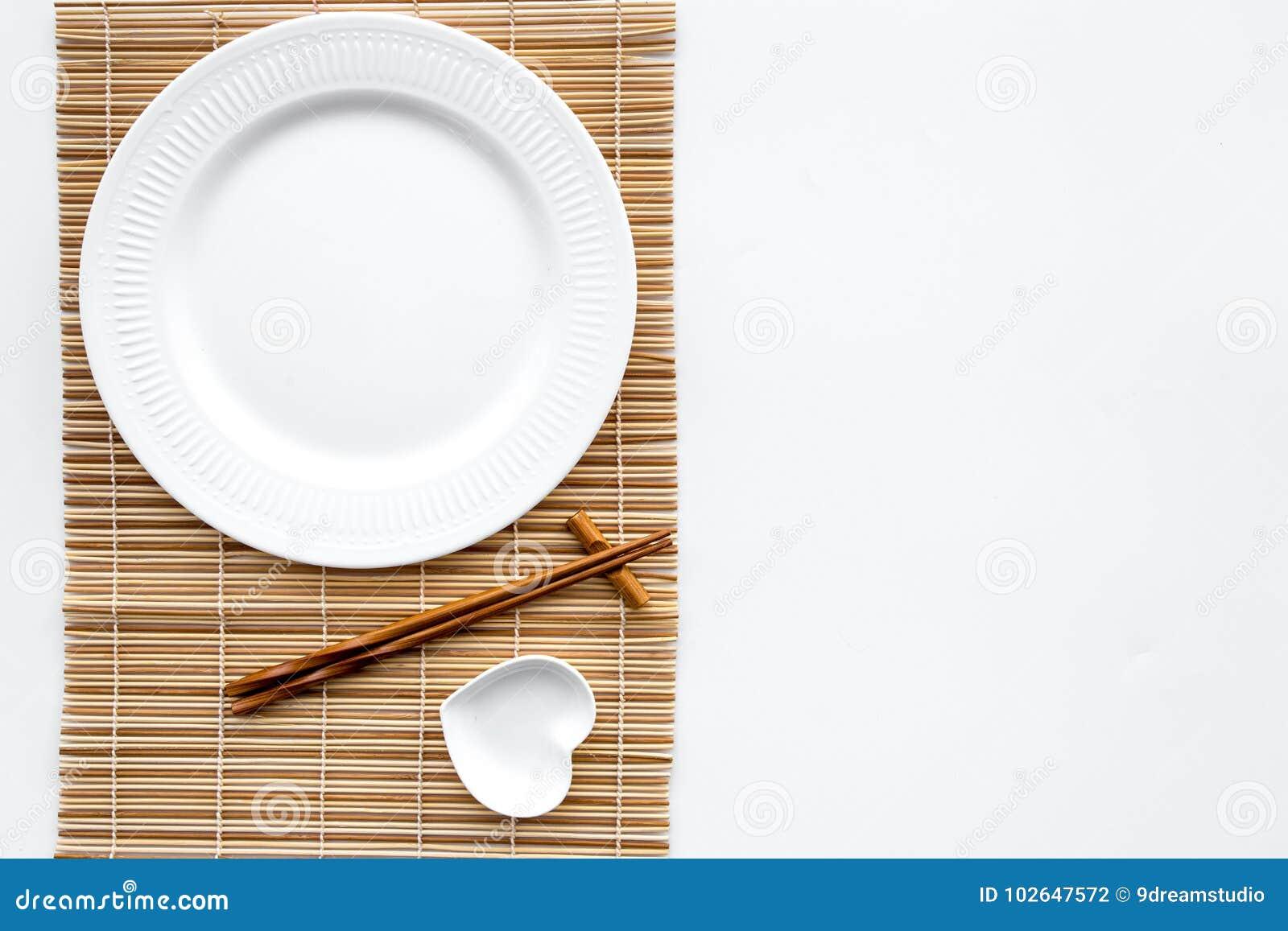Сервировка стола для крена суш Пустая плита на циновке около палочки и шара для sause на белом взгляд сверху предпосылки