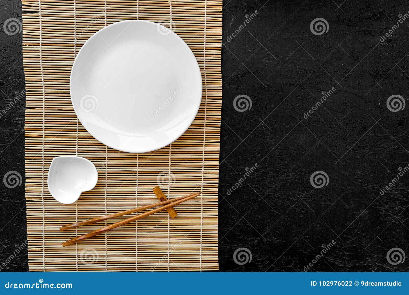 Сервировка стола для крена суш Пустая плита на циновке около палочки и шар для sause на черной столешнице осматривают copyspace