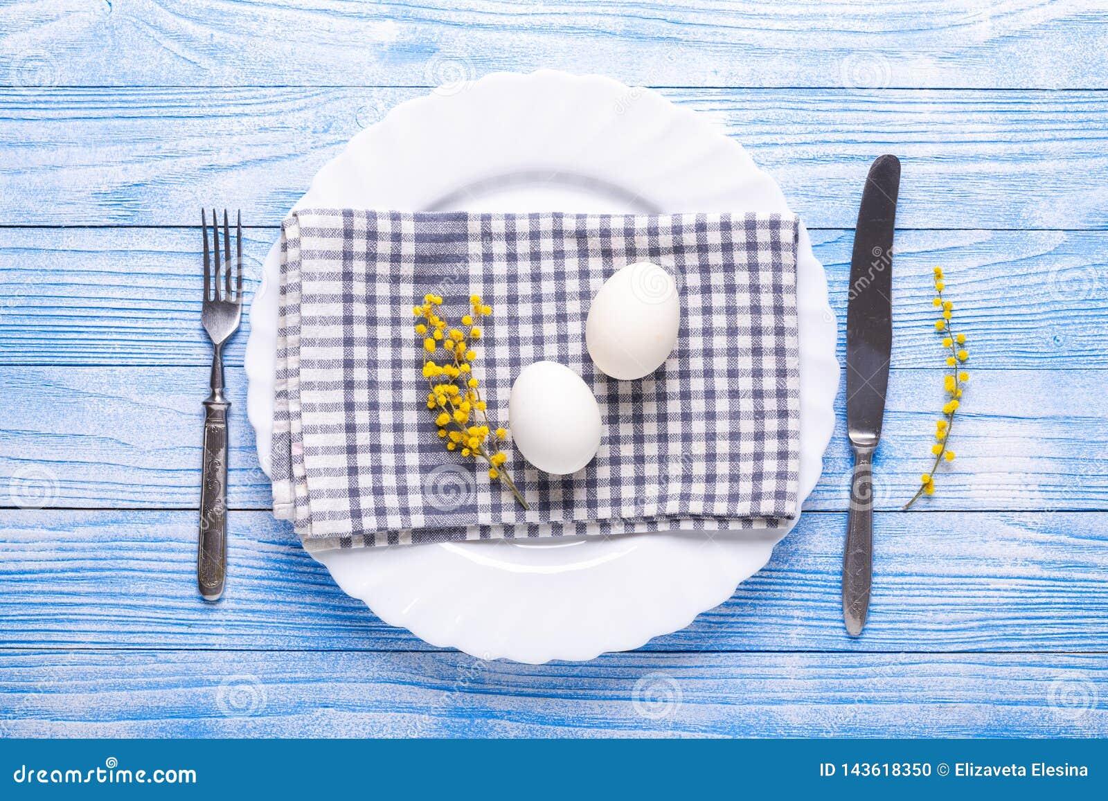 Сервировка стола пасхи Белые яйца, салфетка на плите, цветки мимозы, вилка, нож на голубом деревянном столе